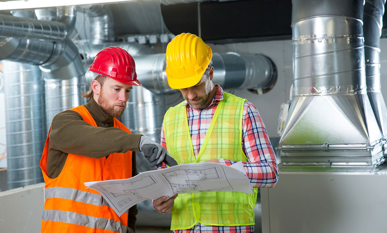 Two men stand together looking at a blueprint. One man is wearing a brown t-shirt with an orange high-vis vest and red hardhat, the other is wearing a red and white plaid shirt with a yellow high-vis vest and matching hardhat.