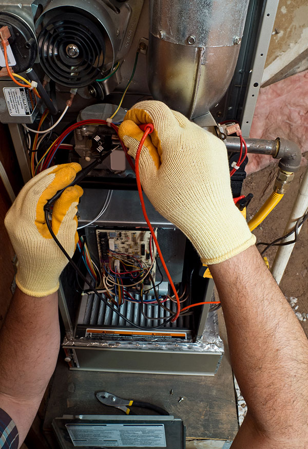 Yellow-gloved hands inside an HVAC system soldering two red wires.
