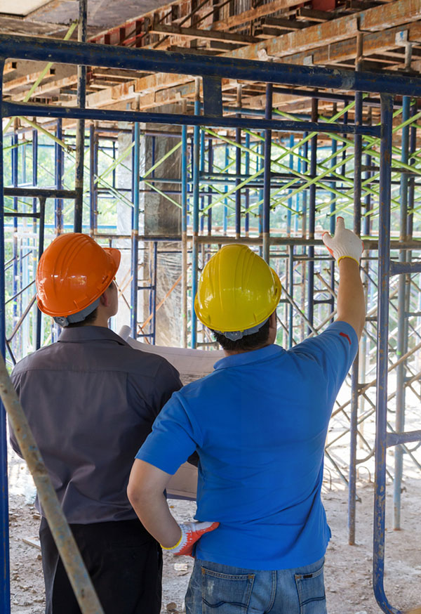 Two mend stand together looking upward at an unfinished ceiling. The man on the left is wearing a grey shirt, orange hardhat, and is holding a blueprint. The man on the right is in a blue shirt and yellow hardhat and is pointing upwards with a white and orange gloved hand.