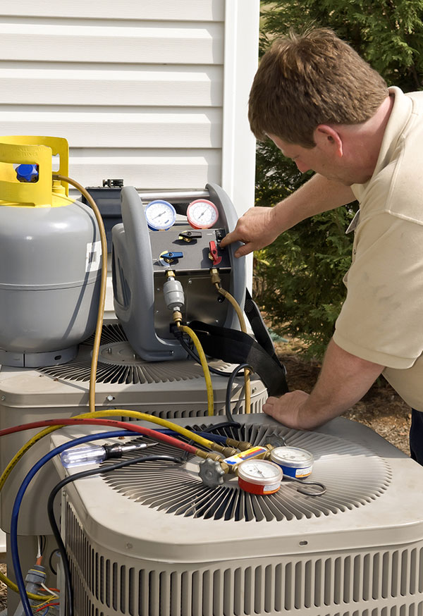 A man in a tan t-shirt stands against an outdoor HVAC unit, with one hand adjusting a red knob.