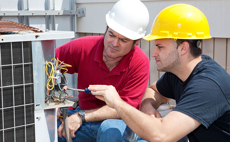 Two men are kneeling at an outdoor HVAC unit. One man in a red shirt and white hardhat looks on as the other in a black t-shirt and yellow hard hat is pointing at a group of wires with a blue screwdriver.